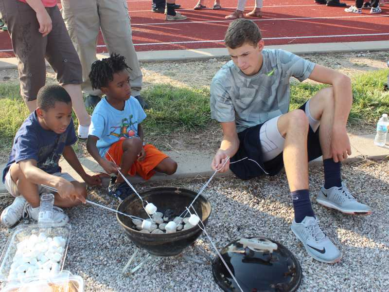 Sophomore Tanner David roasts marshmallows with two Open House attendees at the Language Arts booth. Photo by Walters