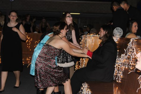 Students seen trying to drag their friend to the dance floor.