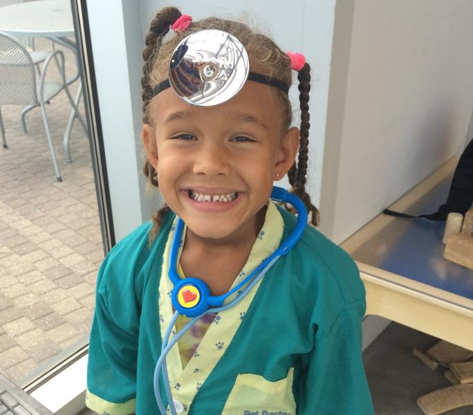 Karissa Kai Patterson, Keyanna Patterson's younger sister, grins in the Veterinarian Clinic exhibit in the Exploration Place.