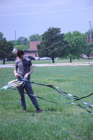 Senior Ian Gaza releases the tail ribbons of a kite.