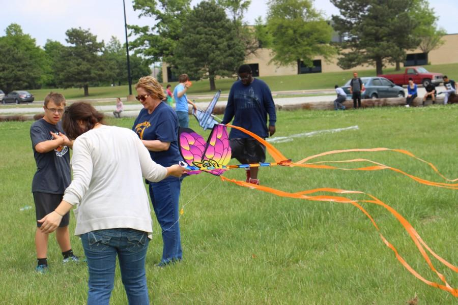 Sophomore Blake Unrein and government teacher Lori Wallentine gather string while senior Sarena Leyba holds the kite.