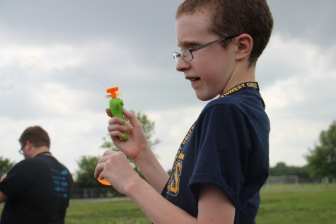 Freshman Taylor Parsons holds a bubble-blowing toy while watching others fly kites.