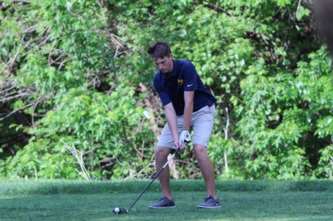 Sophomore Ethan Allen setting up to hit the golf ball at MacDonald golf course Monday, April 25.