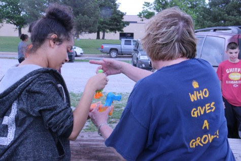 Wallentine and senior Sierra Pierce work on gathering up bubble solution and toys.