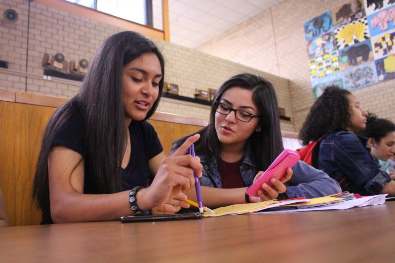 AVID students Irene Delarosa and Fabiola Delatorre work on homework together during lunch. AVID is one of many programs at risk of being cut due to budget constraints.