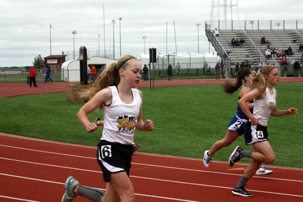 Caroline Fincham(9) and Madi Harkins(9) run the 800 meter on March 30 at the Maize JV track meet. Photo by Bloom