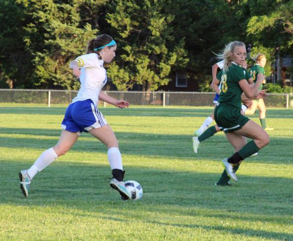 Kick it up a notch. Junior Whitney Weiford kicks the ball toward her teammate while trying to guard it from an opposing player on Tuesday at the Varsity soocer game against Bishop Carroll. Prior to the game, the soccer team could not warm up due to senior night, but still tried their best.