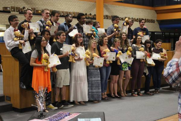 Senior orchestra and band members stand together after accepting their awards