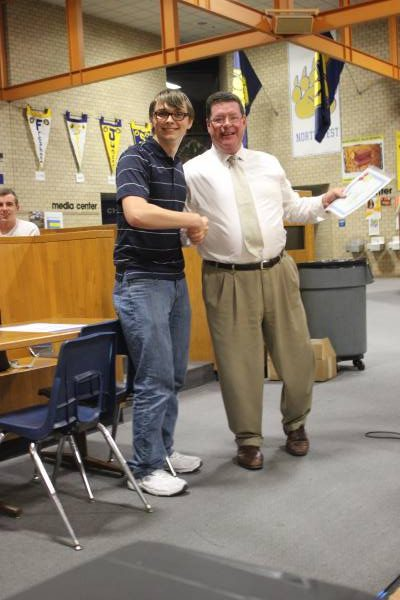 "Chris Kliewer shakes hands with Dr. Leopold. He accepted an award for outstanding achievement and participation. ""I did this for you, i hope you got a picture,"" Kliewer said."