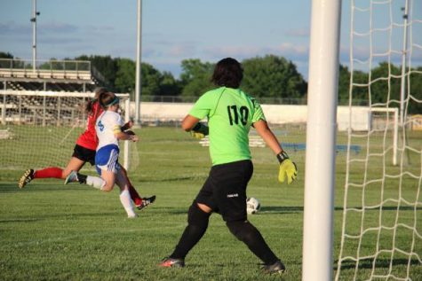 Defender Whitney Weiford (11) fights to beat Maize player to ball as goalie Nia Baker (9) prepares.