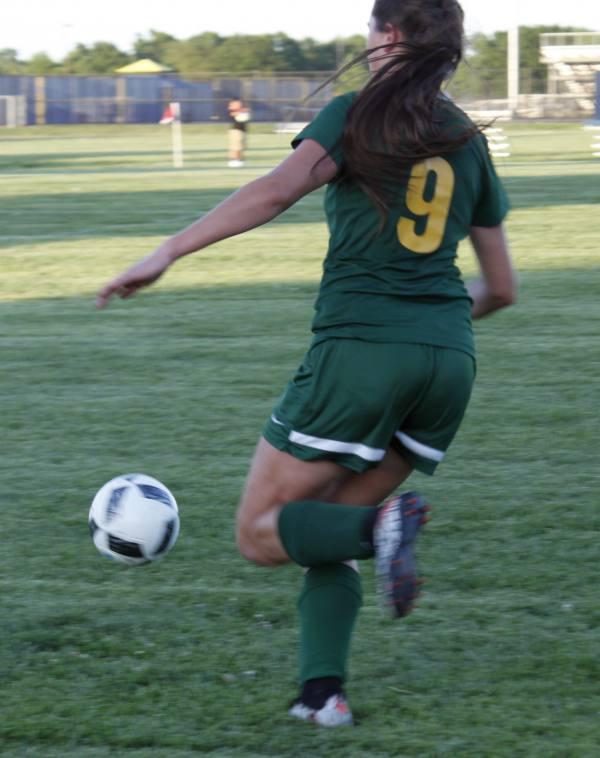 Bishop Carroll sophomore, Hanleigh Allen, kicks the ball soccer ball toward her teammate.