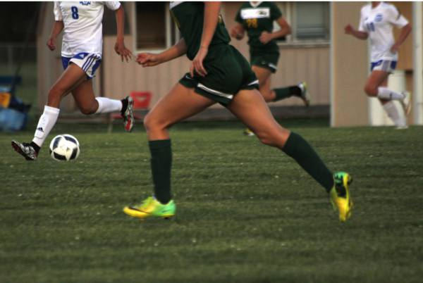 Bishop Carroll junior, Whitney Bockover, and Northwest sophomore, Abril Lucio, race to kick the ball at the Varsity soccer game on Tuesday.