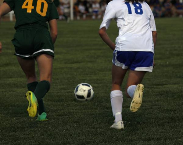 Bishop Carroll sophomore, Whitney Bockover, and Northwest freshman, Brittan Murray, race to kick the ball.
