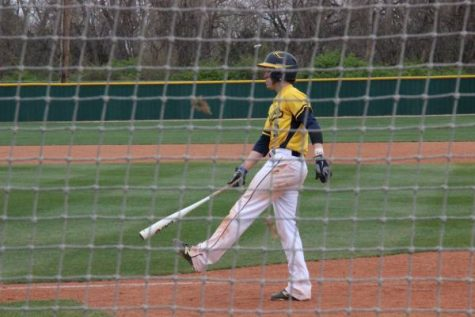 Aaron Rhodes waiting to go up to bat against Olathe East