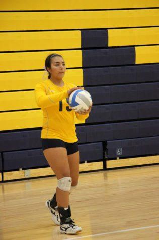 Senior Bella Soliz preparing to serve the ball.