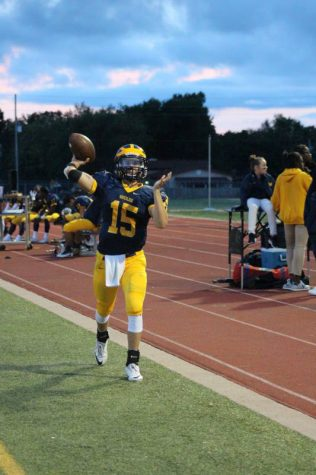Junior Austin Anderson warms up on the sidelines by passing the ball.