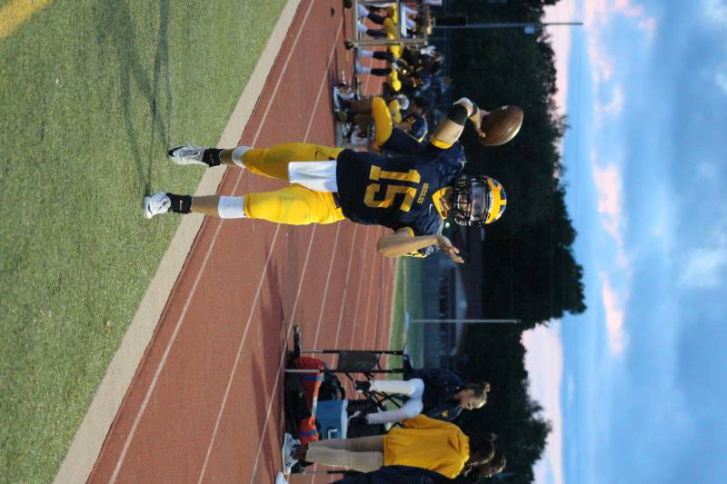 Junior Austin Anderson warms up on the sidelines while passing the ball.