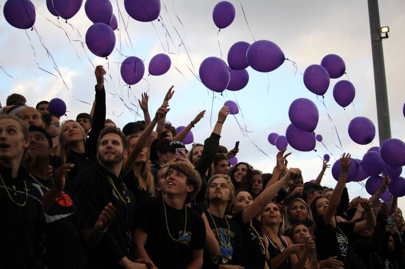 The student section releases purple balloons for Dalton Houle.