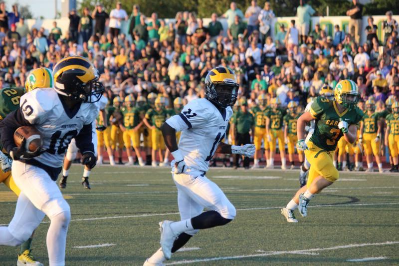 Junior Jaxson Reynolds carries the ball as Senior Martese Mullins runs beside him.