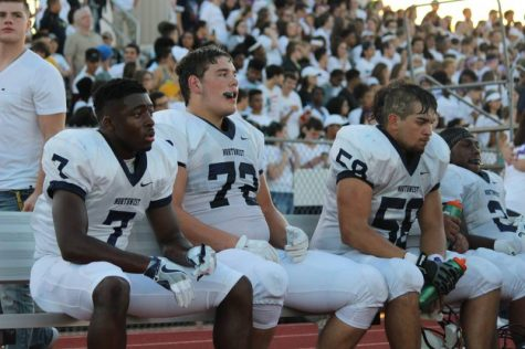 Junior Jalen Smith and Seniors Joey Gilbertson and Angel Washee sit on the bench watching their teammates play.