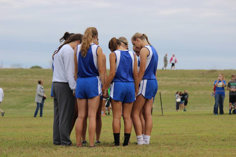 The girls varsity cross country team huddles up to pray before the race.