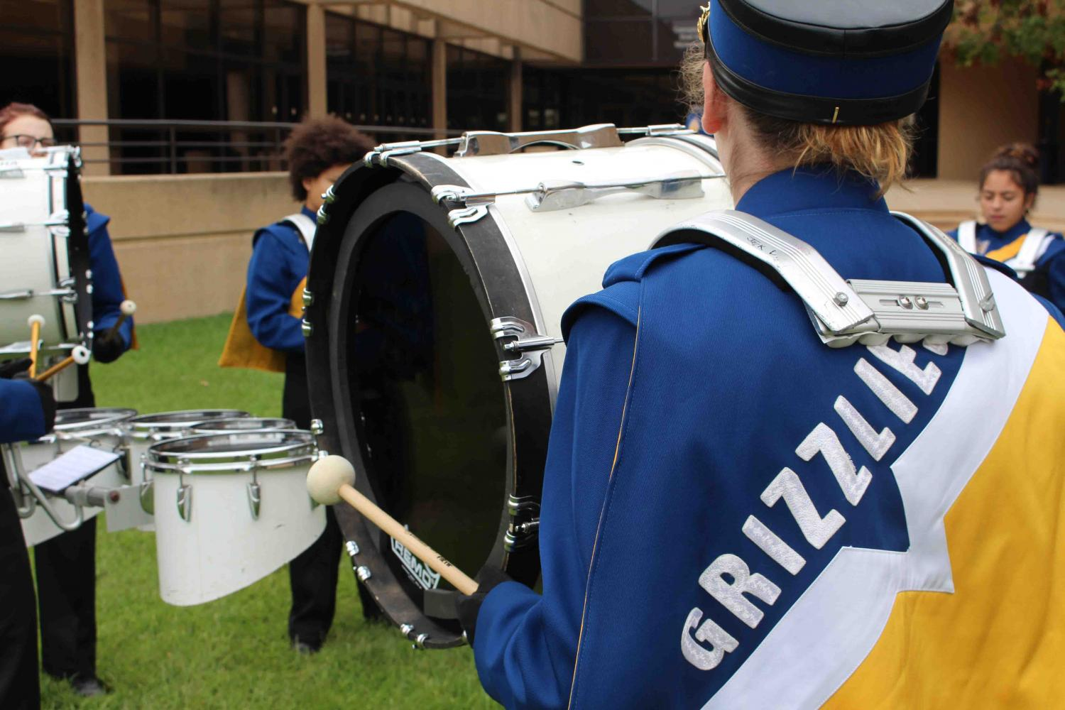 A percussionist plays the bass drum while practicing outside of Century II.