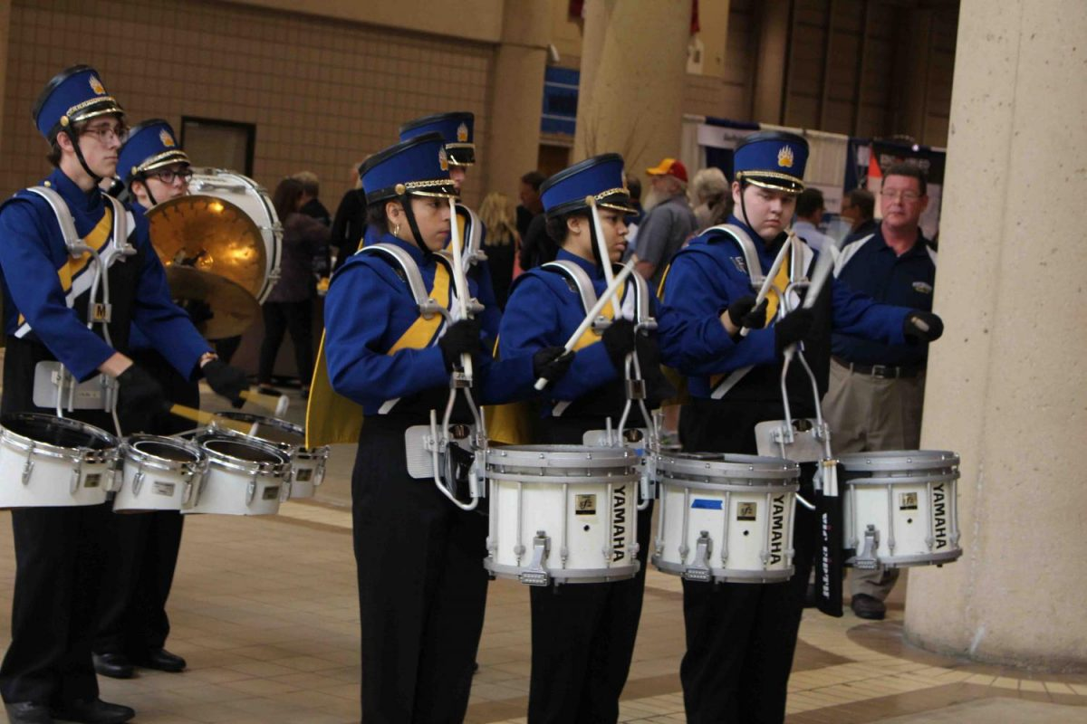 The drumline plays their cadences while standing in place as the crowd gathers around them.