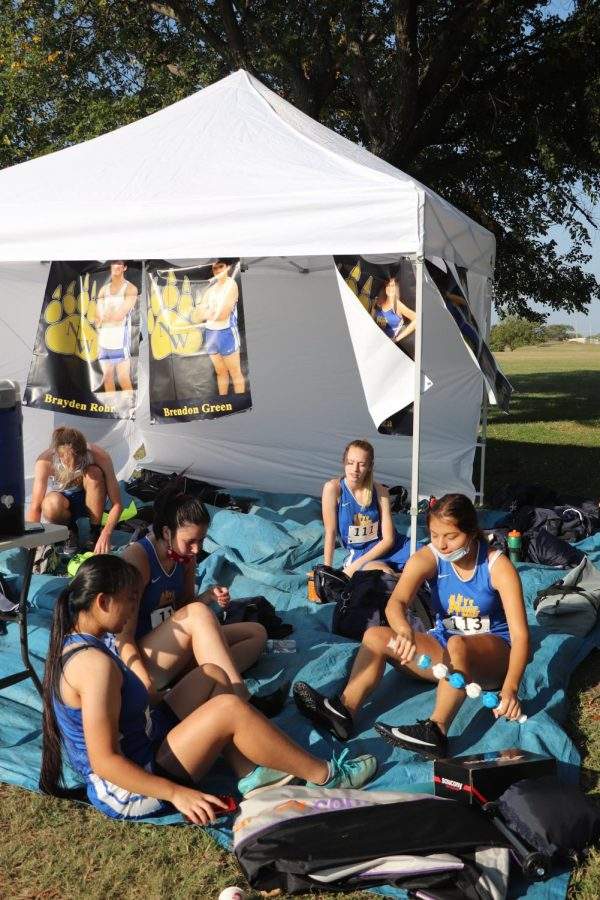Members of the girls team relax and get loose before their run at the Cessna Activity Center on Sept. 29.